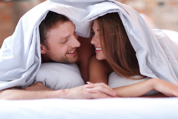 Lindo casal na cama debaixo das cobertas.