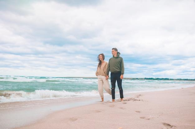 Lindo casal na praia com céu nublado
