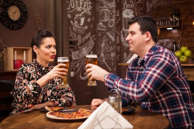 Lindo casal no novo pub, apreciando sua cerveja. pub moderno.