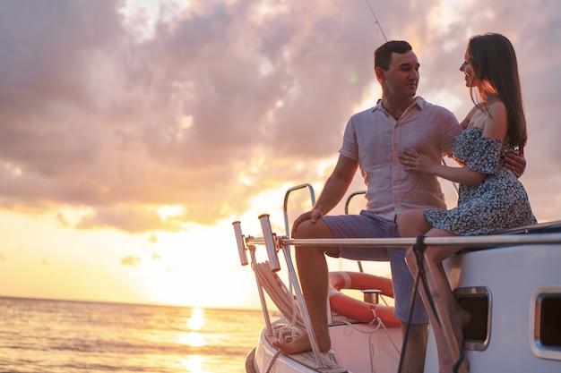 Lindo casal olhando o pôr do sol do iate