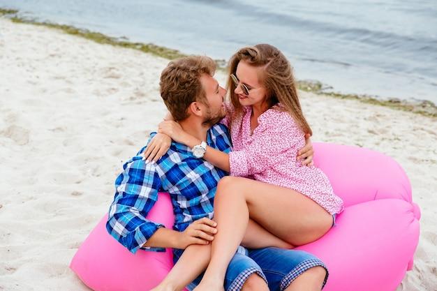 Lindo casal olhando para o outro, sentado no sofá de ar rosa lamzac, na praia
