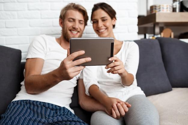 Lindo casal olhando tablet sorrindo sentado no sofá em casa.