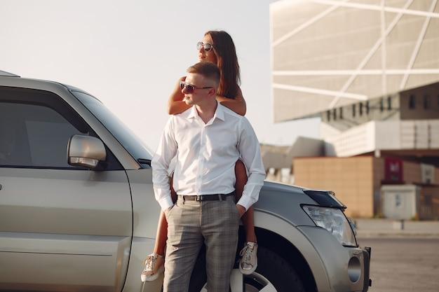 Lindo casal passa o tempo em um parque de verão perto de um carro