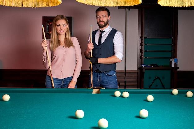 Lindo casal passa um agradável passatempo jogando bilhar, descanso em família, entretenimento, férias