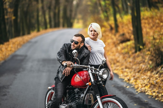 Lindo casal perto de motocicleta vermelha na estrada na floresta