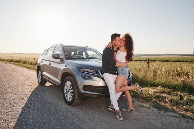 Lindo casal perto de seu carro novo e moderno no fim de semana.