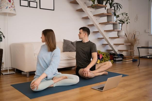 Lindo casal praticando ioga juntos em casa usando um laptop, tendo aulas de ioga online