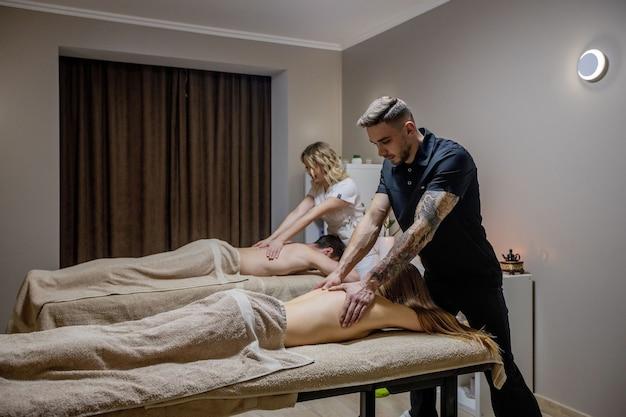 Lindo casal recebendo massagem nas costas, spa de fim de semana para casal