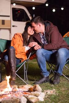 Lindo casal recriando ao longo da fogueira nas montanhas com sua van retrô ao fundo.