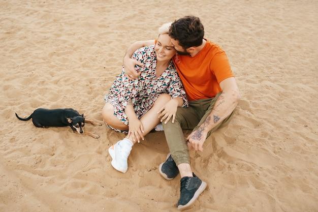 Lindo casal relaxando na areia se abraçando e beijando enquanto brinca com seu cachorro positivo