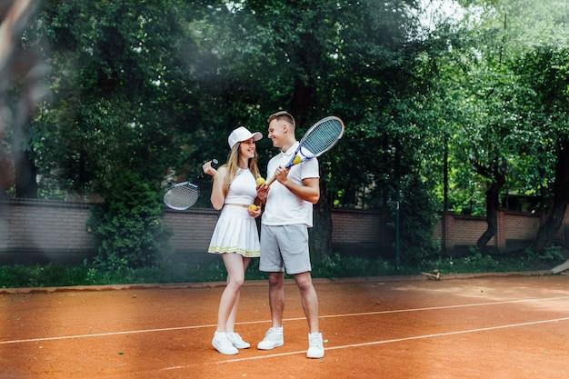 Lindo casal relaxante depois de jogar o jogo de tênis fora no verão. falando sobre a vida.