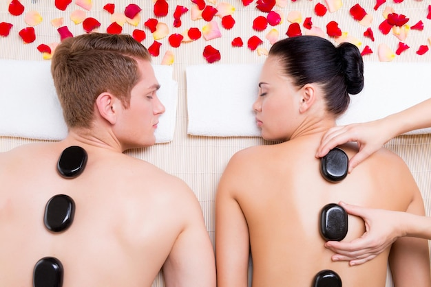 Lindo casal relaxante no salão spa com pedras quentes no corpo. terapia de tratamento de beleza.