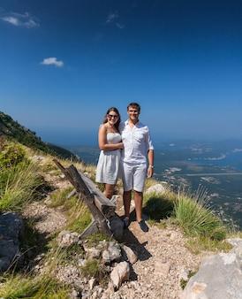 Lindo casal romântico se abraçando no topo de uma montanha alta