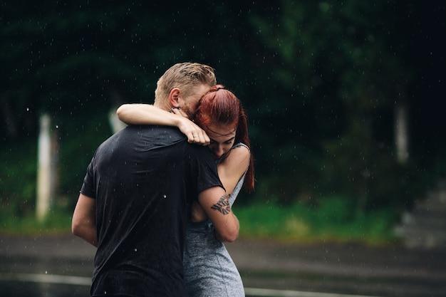 Lindo casal se abraçando do lado de fora na chuva