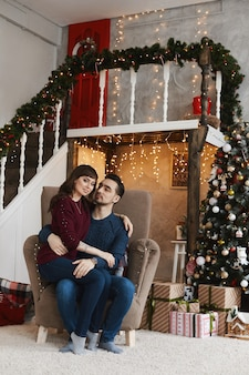 Lindo casal se abraçando na poltrona no interior de uma sala decorada para o natal
