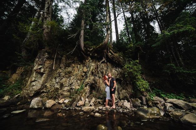 Lindo casal se abraçando perto de um rio na montanha