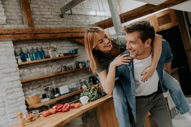 Lindo casal se divertindo juntos na cozinha rústica