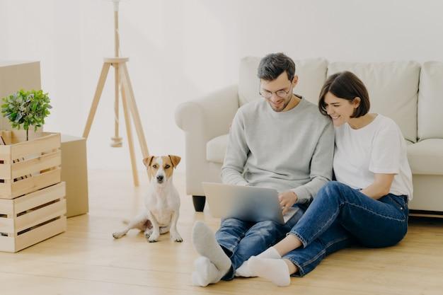 Lindo casal se muda para uma nova habitação, usa laptop moderno para pesquisar idéias de design para seu apartamento