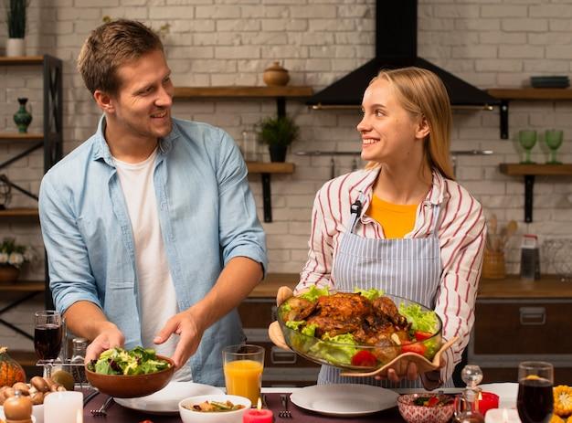 Lindo casal segurando a comida e olhando um para o outro