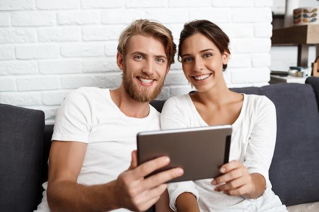 Lindo casal segurando a tablet sorrindo para casa.
