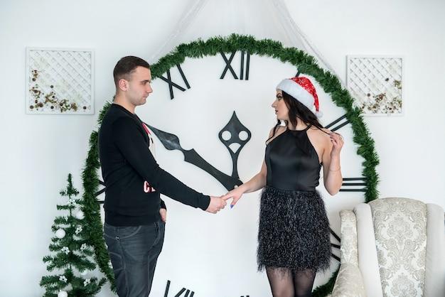 Lindo casal segurando as mãos contra um grande relógio