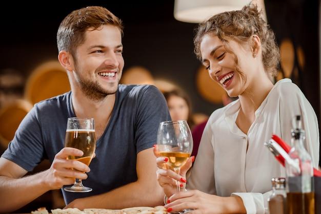 Lindo casal segurando copos de vinho branco e cerveja no restaurante.