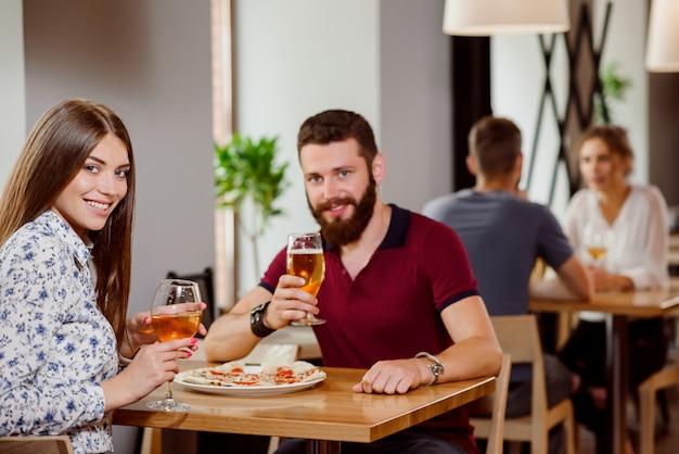 Lindo casal segurando copos de vinho e cerveja na pizzaria.