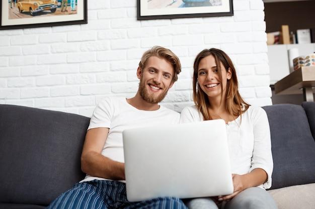 Lindo casal segurando laptop sorrindo para casa.