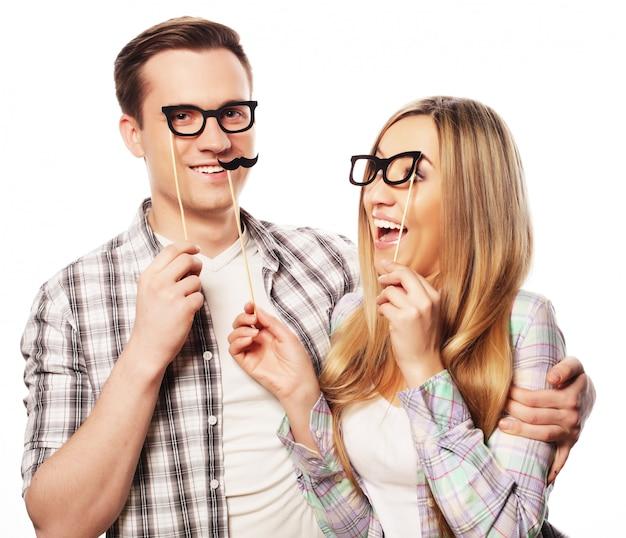 Lindo casal segurando óculos de festa na vara