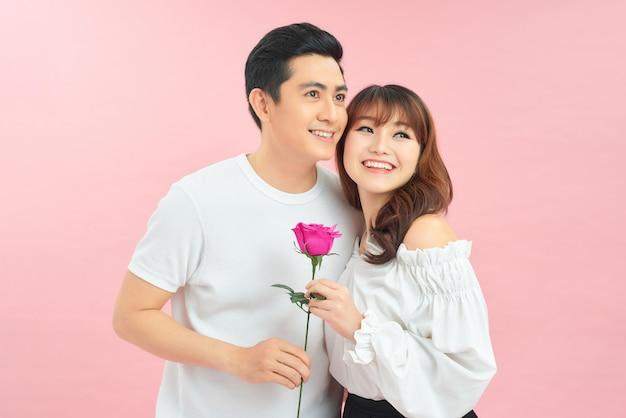 Lindo casal segurando uma flor em fundo rosa