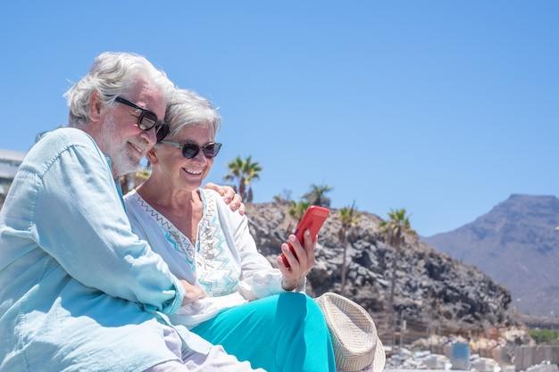 Lindo casal sênior abraçando ao ar livre enquanto usam o telefone celular juntos.