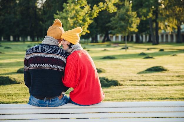 Lindo casal senta no banco juntos, veste roupas quentes e chapéus de malha, se abraçam