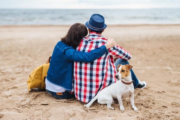 Lindo casal senta-se na praia, perto do mar, abraça-se, conversa agradável, admira a natureza e seu cachorrinho senta-se perto dos anfitriões
