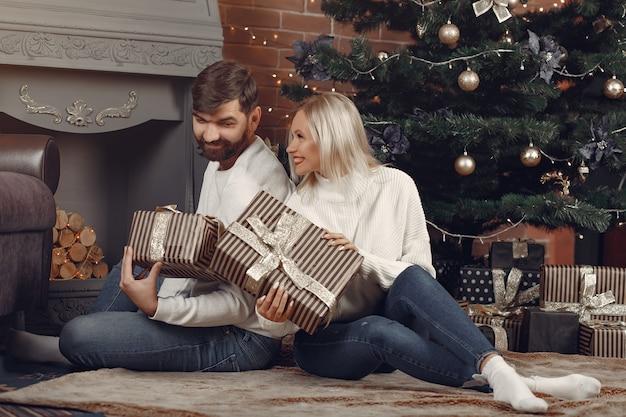 Lindo casal sentado em casa perto da árvore de natal