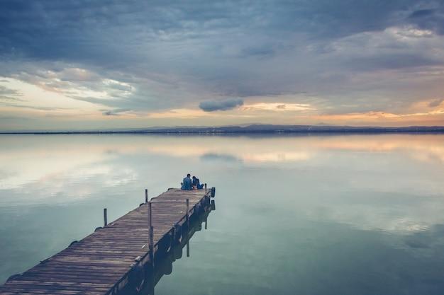 Lindo casal sentado em uma doca de madeira sob um lindo céu ao pôr do sol