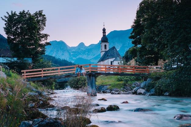 Lindo casal sentado em uma ponte sobre um rio com montanhas e uma igreja ao fundo, em ramsau, alemanha, em berchtesgaden.