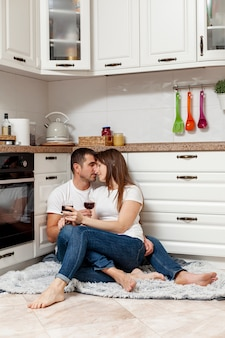 Lindo casal sentado no chão e segurando copos com vinho
