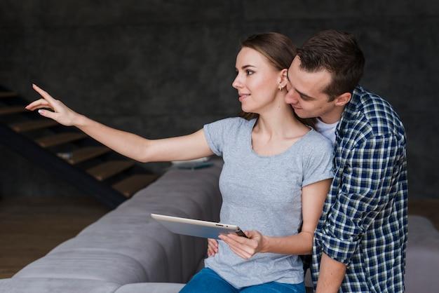 Lindo casal sentado no sofá com tablet