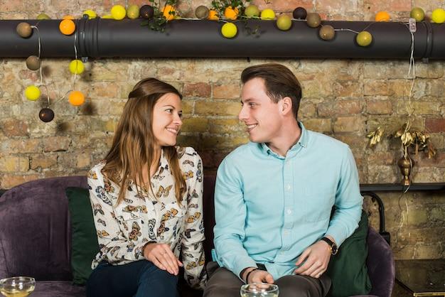 Lindo casal sentado no sofá e olhando um ao outro