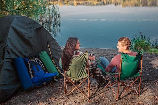 Lindo casal sentados juntos em cadeiras dobráveis na água e nos olhar. eles sorriem. ela segura a xícara nas mãos e coberta com o cobertor. existem tendas e equipamentos também.
