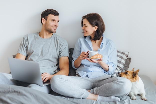 Lindo casal, sentados juntos na cama, usam o laptop, têm uma conversa agradável entre si