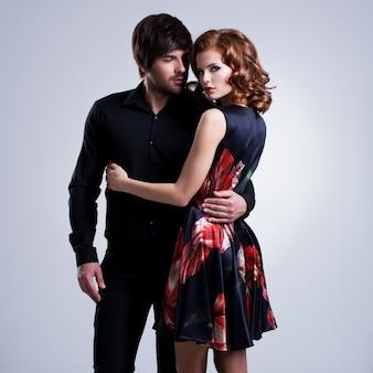 Lindo casal sexy apaixonado em pé sobre um fundo cinza