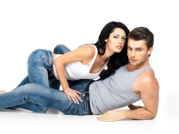 Lindo casal sexy apaixonado em um espaço em branco vestido de jeans azul e camiseta branca