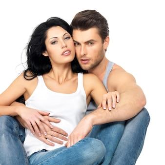 Lindo casal sexy apaixonado na parede branca vestido de jeans azul e camiseta branca