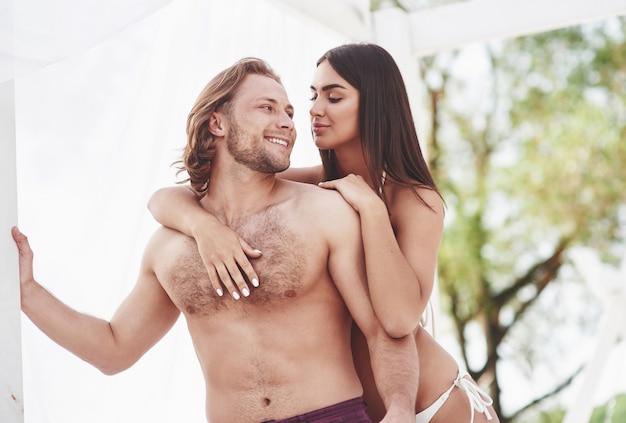 Lindo casal sexy cara e garota vestindo roupas de banho quando na praia. romântico deitado na areia