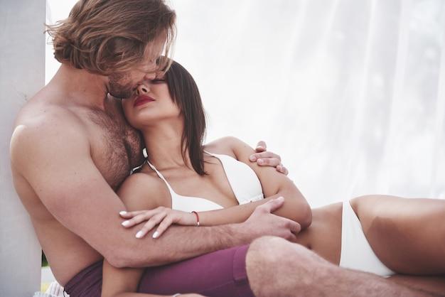 Lindo casal sexy rapaz e garota vestindo trajes de banho quando na praia. romanticamente deitado na areia.
