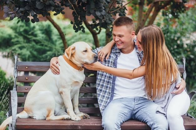Lindo casal sorridente com seu cachorro no parque em um dia ensolarado