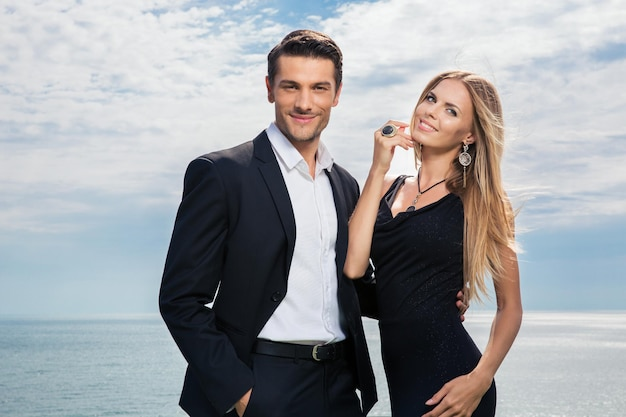 Lindo casal sorridente em pé junto com o mar na parede
