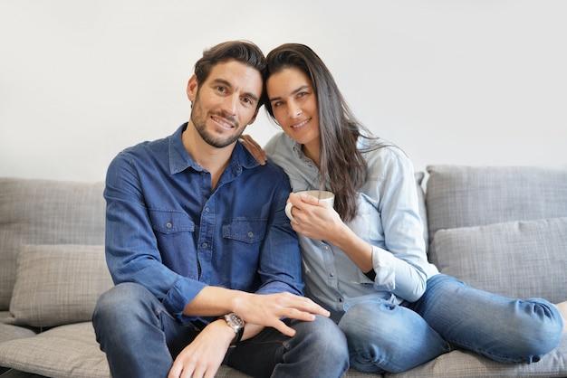 Lindo casal sorridente isolado em denim no sofá confortável