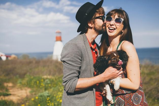 Lindo casal sorridente jovem elegante e moderno apaixonado, caminhando com um cachorro no campo